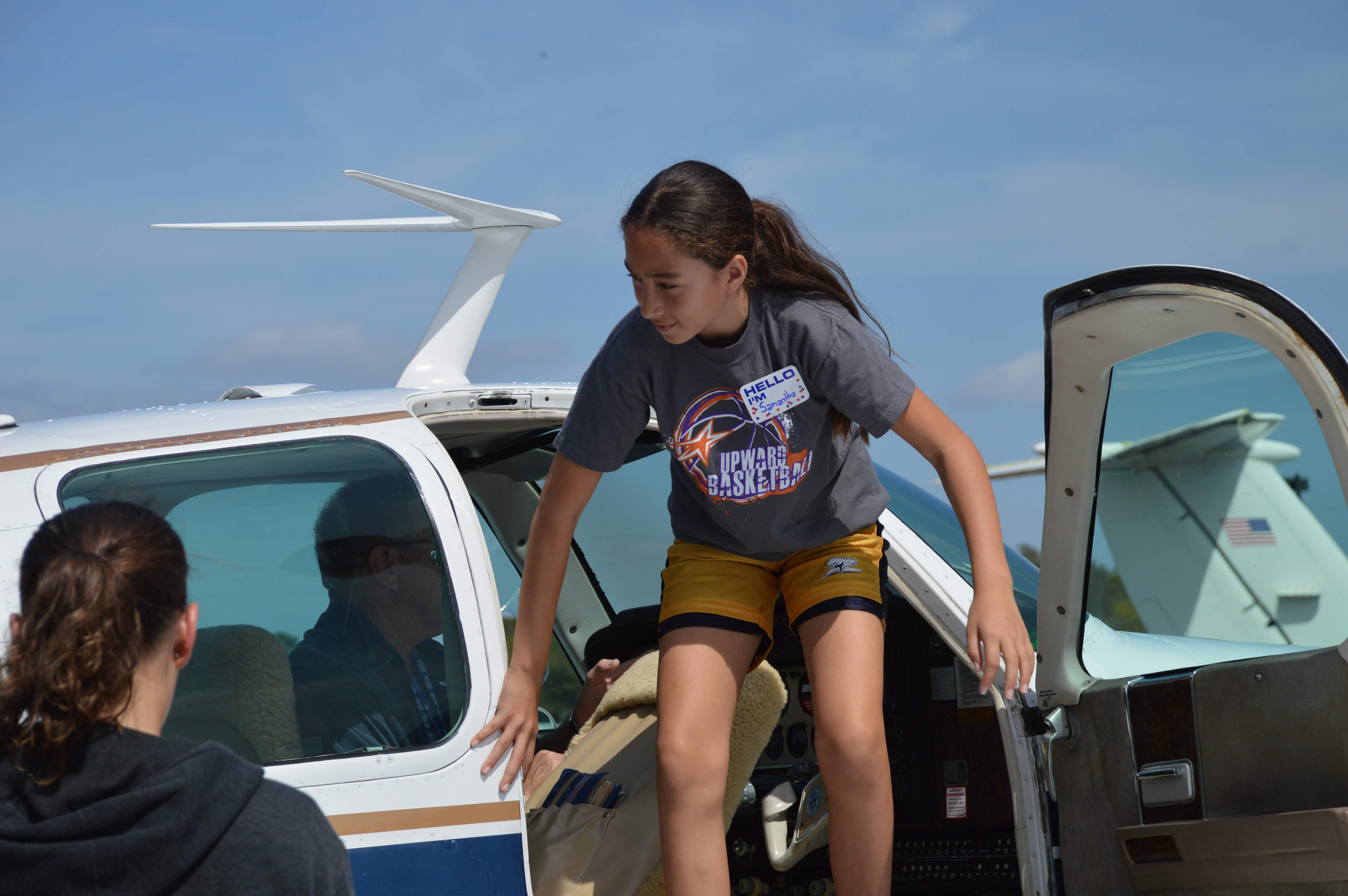 Samantha Jaksetic climbing out of aircraft after flight.