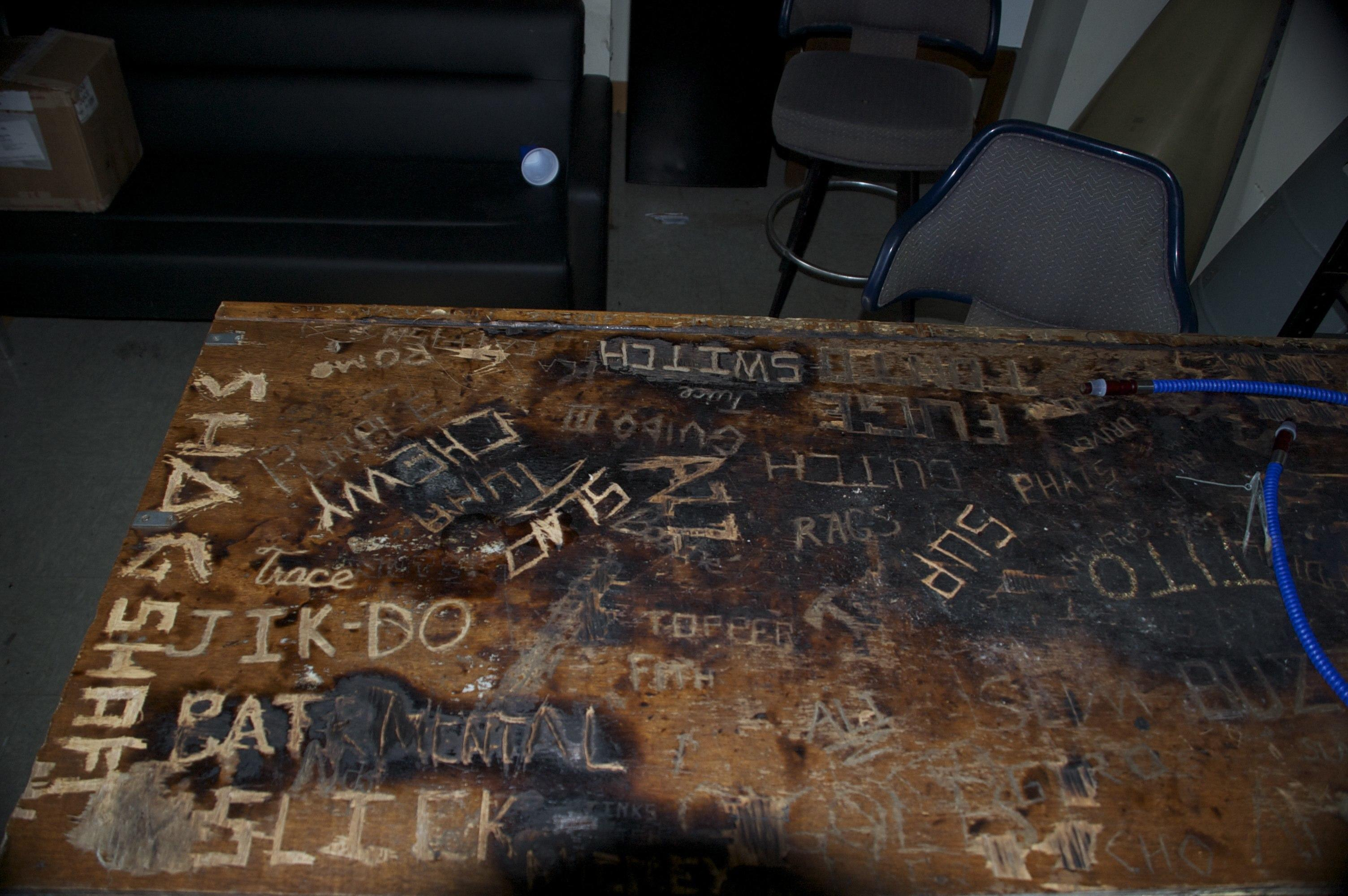 Carved names and scorching on bar top.